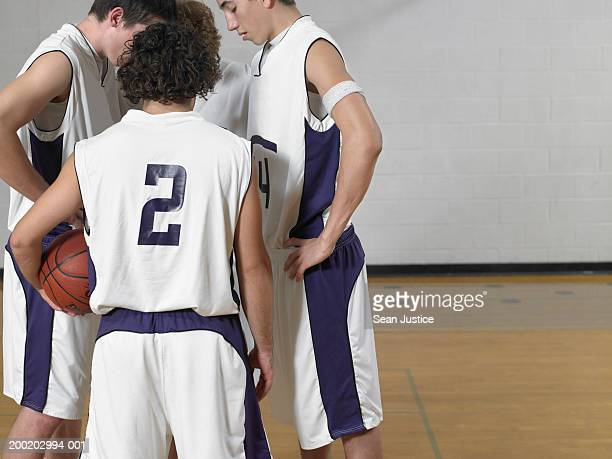 Teenage boys (16-18) basketball players in huddle on court