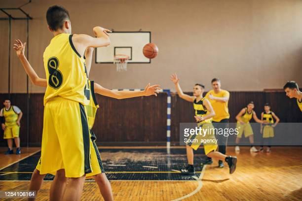 teenage boys basketballspieler beim training drinnen - passing sport stock-fotos und bilder