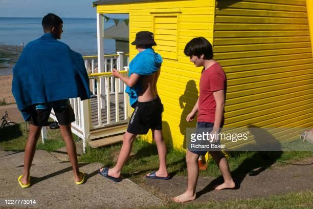 Teenage boys carrying bathing towels walk past a yellow beach hut while enjoying fine summer weather on the seafront promenade at Whitstable on 18th...