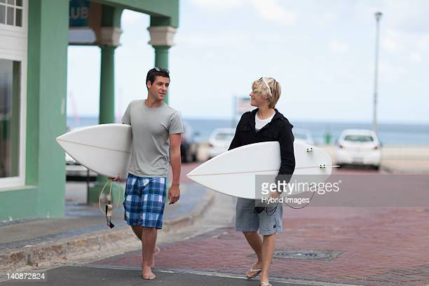 Teenage boys carrying surfboards