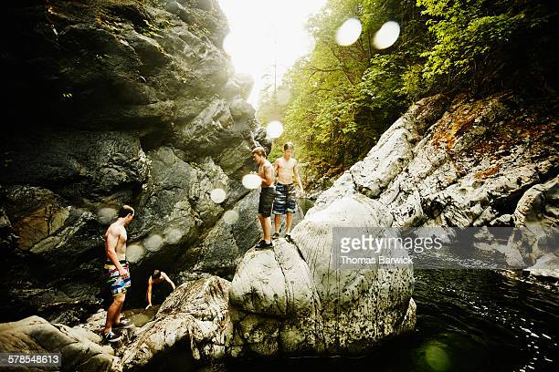 Teenage boys climbing on boulders in river
