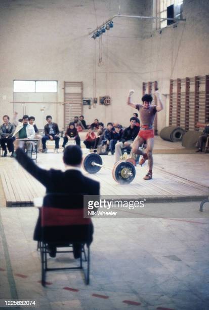 Teenage boys compete in weightlifting competition in school gymnasium in Baghdad circa 1978
