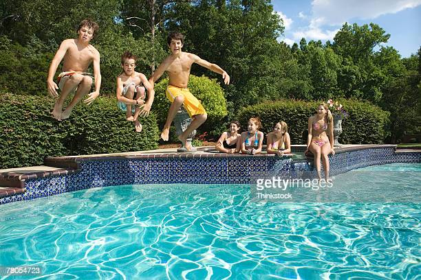 Teenage boys doing cannonballs into pool