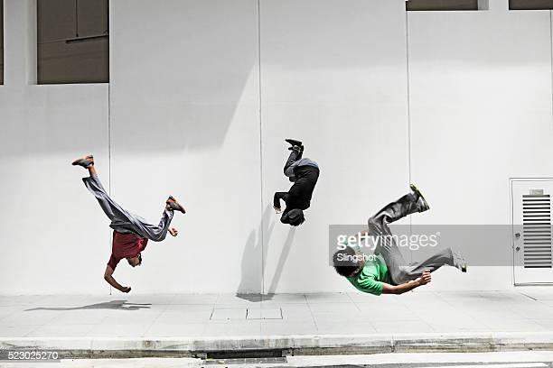 teenage boys doing flips, parkour - le parkour stock-fotos und bilder