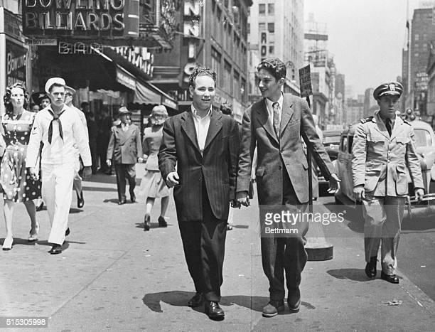 Teenage boys in a subtle version of the zoot suit walk down a city street in 1943 attracting some attention from military and civilian passersby in...
