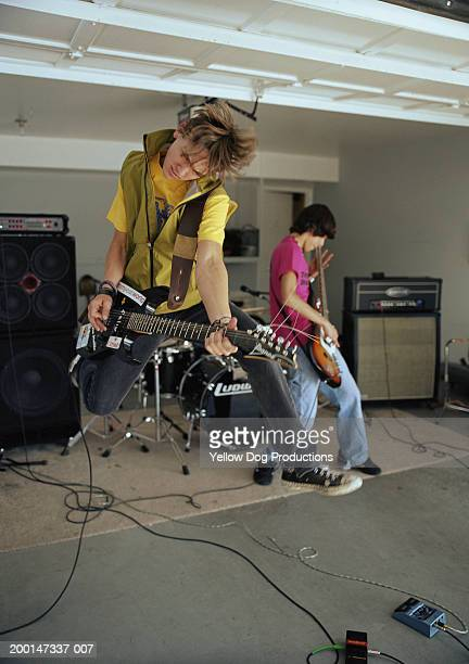 teenage boys (15-17) in band practicing in garage, boy jumping in air - garage band stock photos and pictures