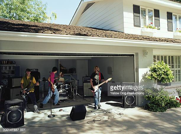teenage boys (15-17) in band practicing in garage - garage band stock photos and pictures