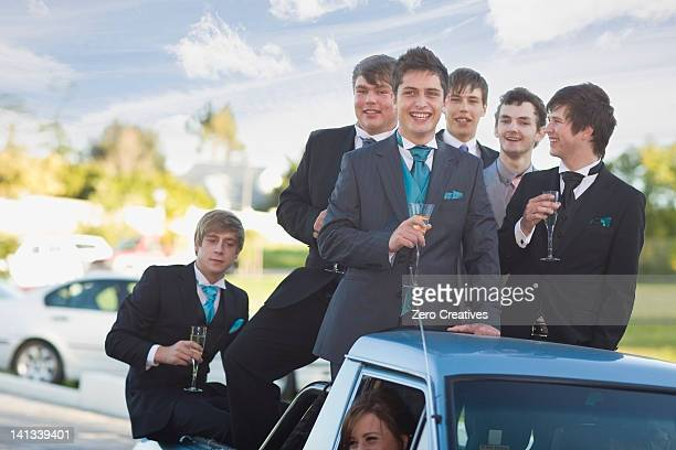 Teenage boys in suits smiling from car