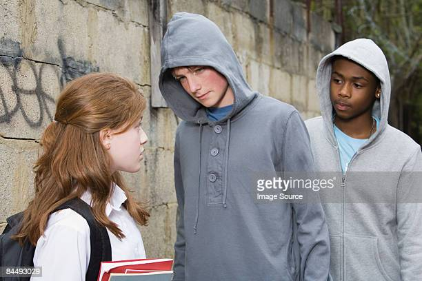 teenage boys intimidating a teenage girl - ominous stock photos and pictures