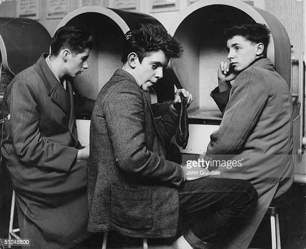Teenage boys listening to the latest record releases in soundproof listening booths at Imhof's Melody Bar in New Oxford Street London 24th November...