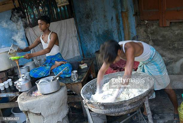 Teenage boys make tea and sweets for sale in a street side tea stall Across India teens and younger work long hours cooking and cleaning in tea shops