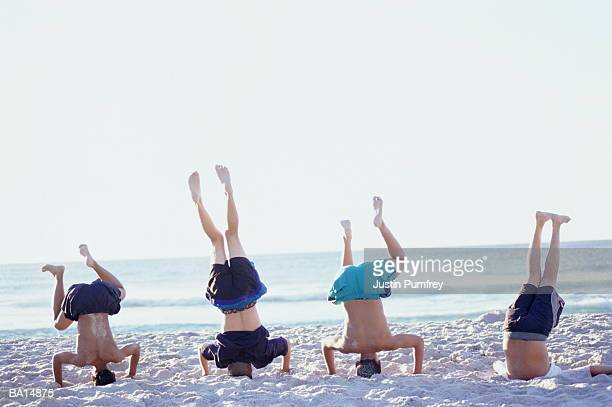 Teenage boys (14-16) on beach performing headstands, rear view
