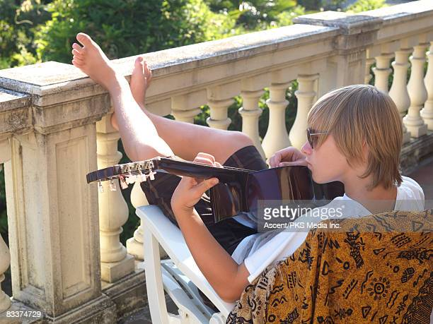 teenage boys on terrace, plays acoustic guitar - teen boy barefoot stock photos and pictures