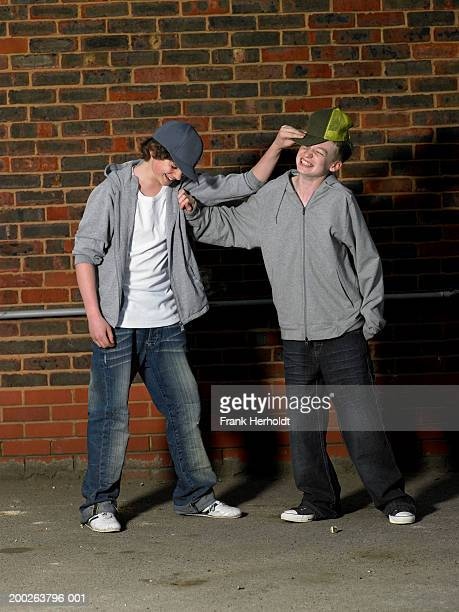 Teenage boys (13-15) play fighting by wall, smiling