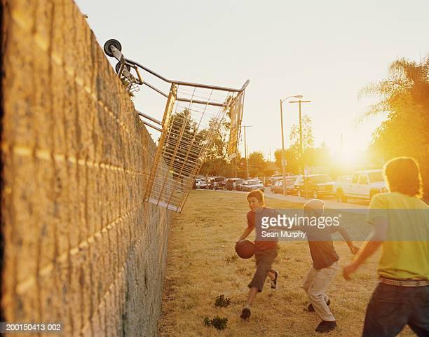 Teenage boys (13-15) playing basketball, using grocery cart for hoop