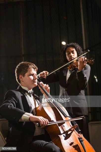 teenage boys playing double bass and violin in concert - classical concert stock pictures, royalty-free photos & images
