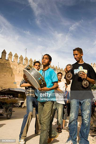 Teenage boys playing music with traditional instruments in the street in the Medina of FaselBali Fez FesBoulemane Morocco