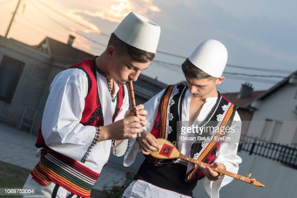 teenage boys playing musical instruments against houses during sunset - albania stock pictures, royalty-free photos & images