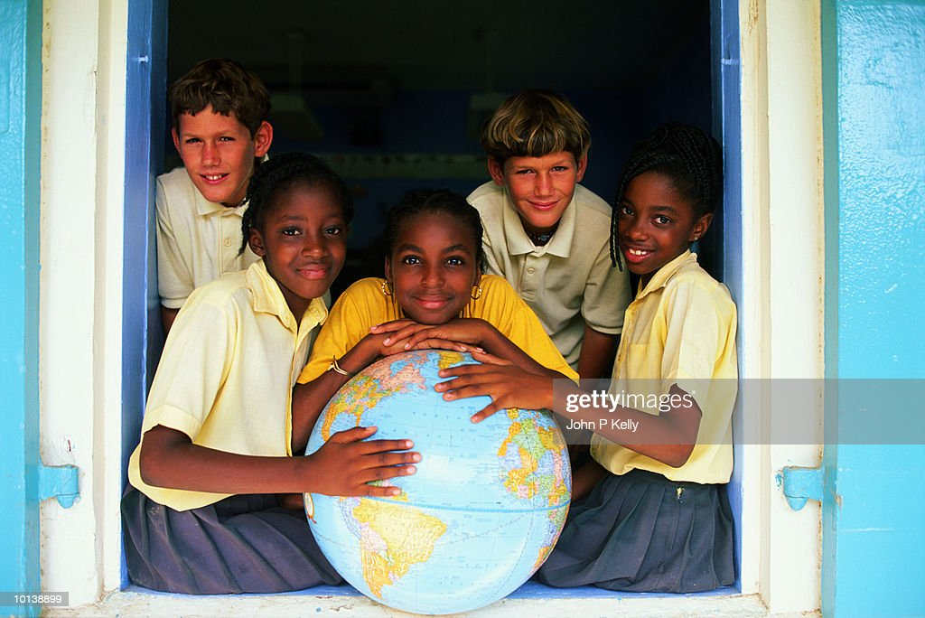 Teenage boys (12-14) posing around large globe : Stock Photo