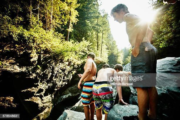 Teenage boys preparing to jump into swimming hole