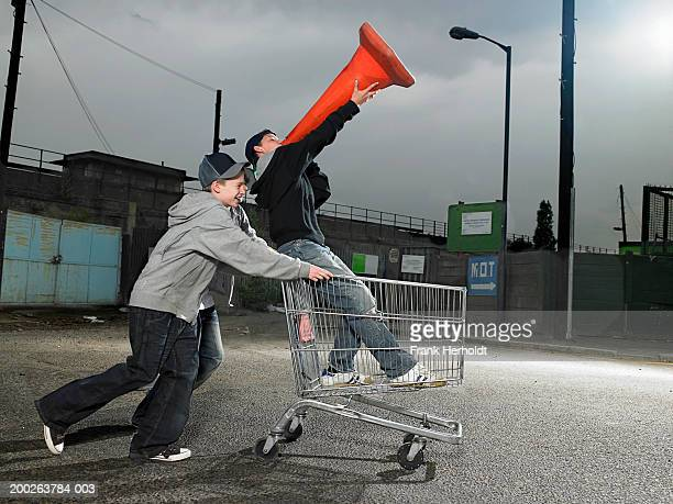 teenage boys (13-15) pushing friend holding traffic cone in trolley - chav stock photos and pictures
