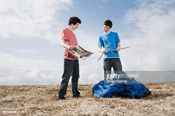 Teenage boys putting up tent