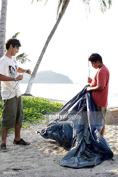 Teenage boys (15-17) setting up tent on beach