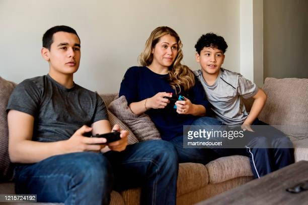 """teenage boys showing mother how to play video games in self-isolation, covid-19. - """"martine doucet"""" or martinedoucet stock pictures, royalty-free photos & images"""