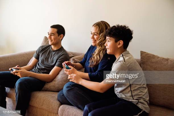 """teenage boys showing mother how to play video games in self-isolation, covid-19. - """"martine doucet"""" or martinedoucet foto e immagini stock"""