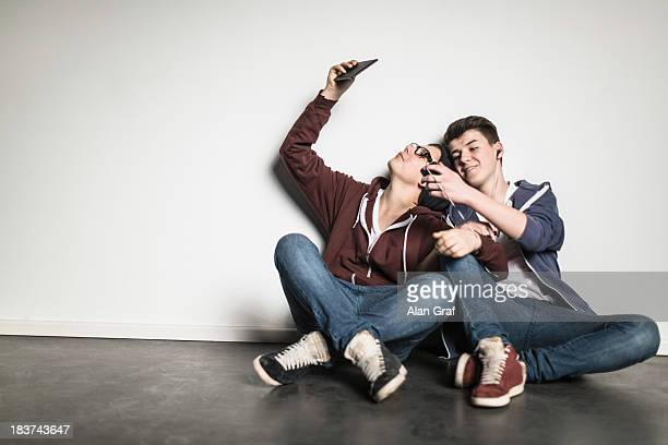 Teenage boys sitting cross legged leaning against wall using smartphones