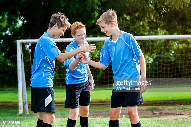 Teenage boys soccer team congratulate one another after winning game