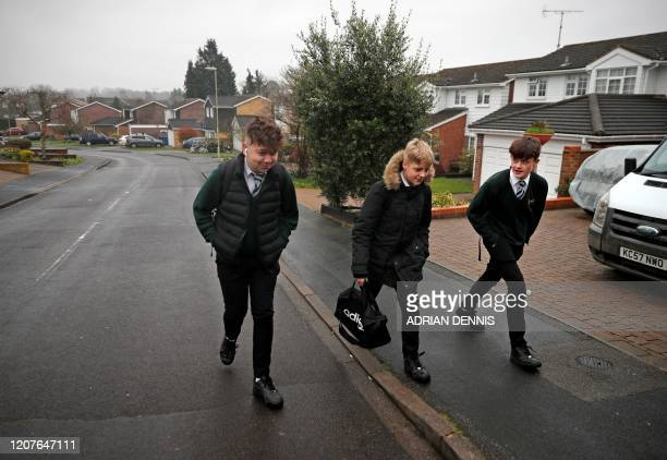 Teenage boys walk to a bus stop in Hartley Wintney west of London on March 19 as they make their way to on their way to Robert May's School Britain...