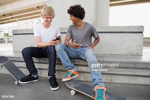 teenage boys with skateboards and cellphone - digital native stock pictures, royalty-free photos & images