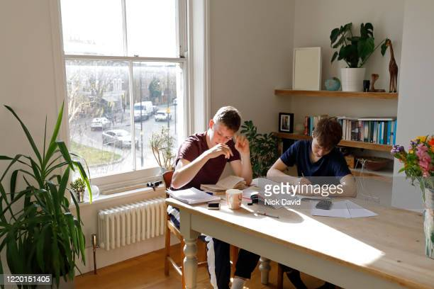2 teenage boys working and studying together at home sitting at the kitchen table.