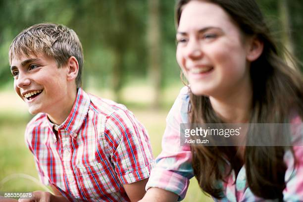 Teenage brother and sister laughing in woodland