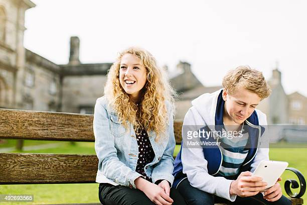 Teenage brother and sister sitting on bench