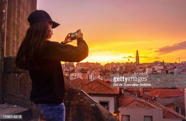 teenage brunette girl dressed in black and wearing a cap wearing a surgical mask during a pandemic, sightseeing, taking photos of the beautiful sunset over the houses in porto - portugal stock-fotos und bilder
