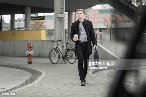 Teenage businessman going to office holding briefcase and coffee cup, Bavaria, Germany
