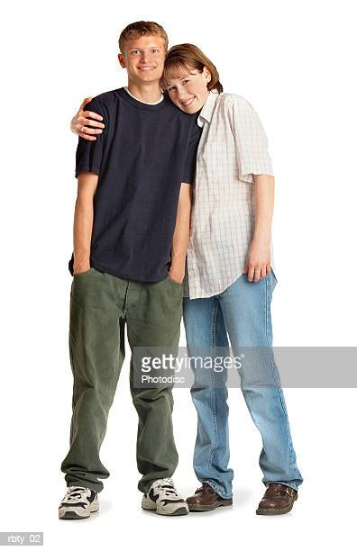 teenage caucasian girl and boy standing close with her arm around him and her head on his shoulder as they smile at the camera