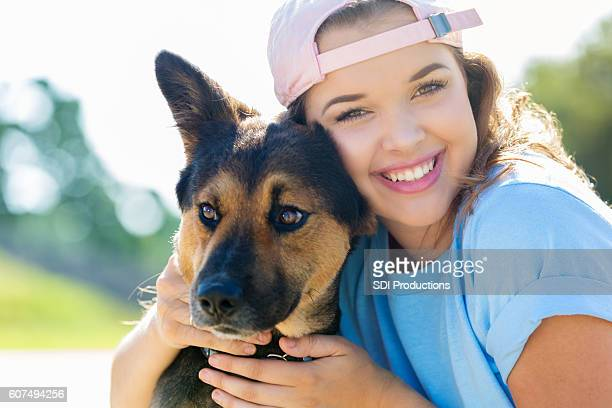 Teenage Caucasian girl hugs her German Shepherd