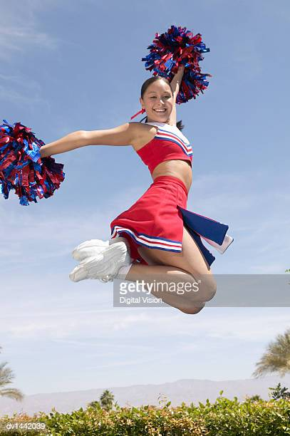 teenage cheerleader holding pompoms jumps for joy - cheerleader up skirt stock photos and pictures
