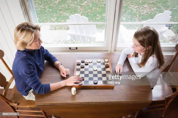 Teenage Children Playing Checkers Chess Game