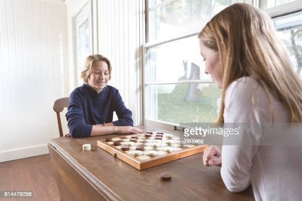 teenage children playing checkers chess game - chequers stock pictures, royalty-free photos & images
