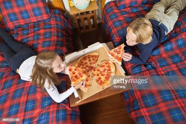 Teenager Kinder teilen Essen Pizza in ihrem Zimmer