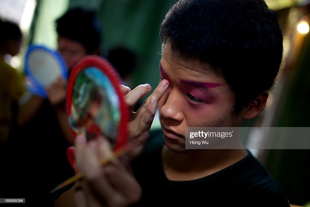 A teenage Chinese Yu Opera performer dresses up to prepare on October 30, 2012 in Zhengzhou, China. As many as 60 performers from the Sanmenxia theatrical troupe are invited to perform Chinese traditional Yu Opera for local villagers in rural Zhengzhou city to celebrate the village's temple fair and earn 10,000 RMB yuan (US$ 1,600) each performance. Yu Opera, also called Henan Bangzi or Ou Opera, is one of the most popular local operas in China. Its earliest written record can be traced back more than 200 years and at the end of the Qing Dynasty (A.D. 1644-1911), the opera became widespread across the Henan province. After the establishment of the People's Republic of China in 1949, it experienced rapid growth not only in the villages and cities of Henan Province but also throughout the country. In recent years its popularity has declined due to young people's attraction to more modern cultures.