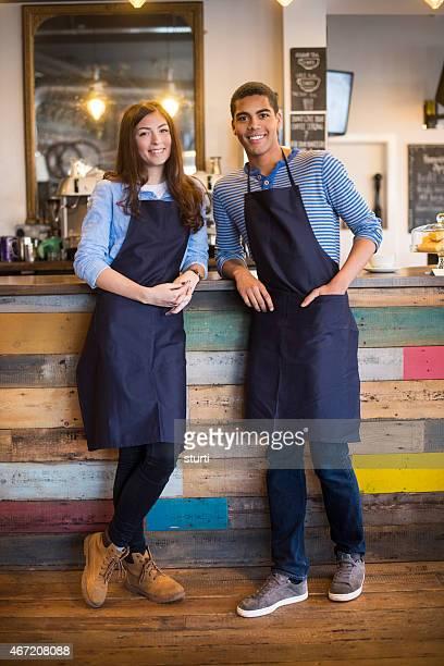 teenage coffee shop waiters smiling to camera