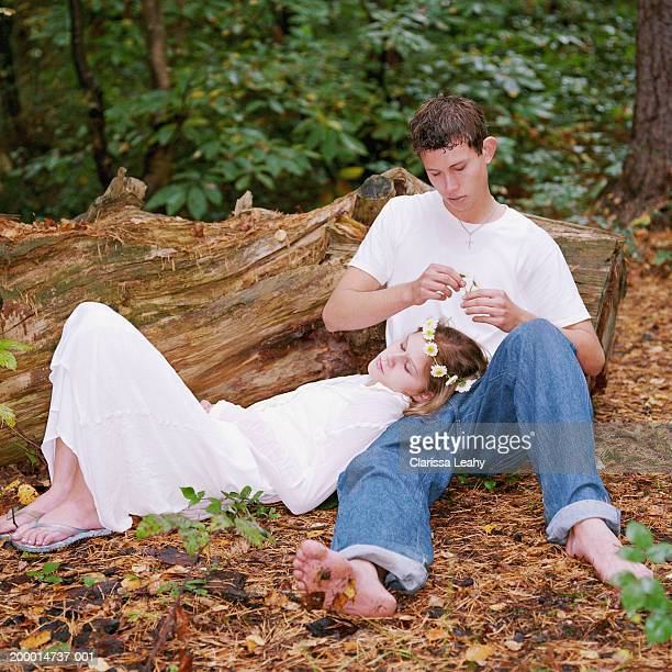 teenage couple (14-16), boy placing flowers on girl's head, outdoors - girl wear jeans and flip flops stock photos and pictures