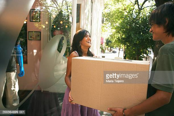 Teenage couple (16-18) carrying box by shop, laughing