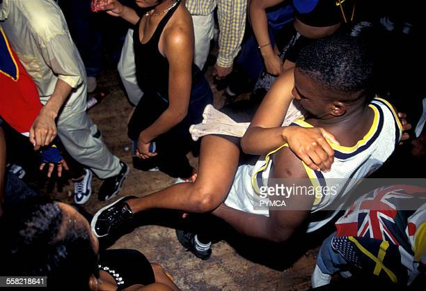 Teenage couple dancing ragga style amongst the crowd at a dancehall party Notting Hill Carnival London 1990s