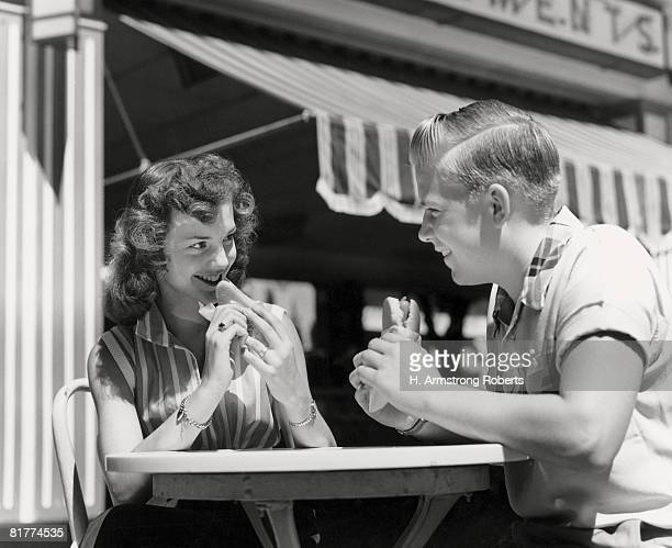 Teenage couple eating hotdogs outside at refreshment stand table.